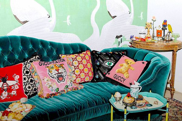 A green velvet settee with embroidered Gucci cushions on it.