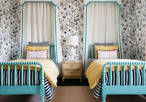 makeover of the week - Bedroom with two twin canopy beds, whimsical wallpaper, and yellow bedding.