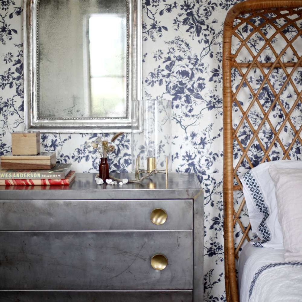 A bedroom with blue floral wallpaper on the walls