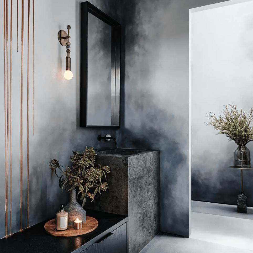 A bathroom with slate gray walls that look like watercolor paintings
