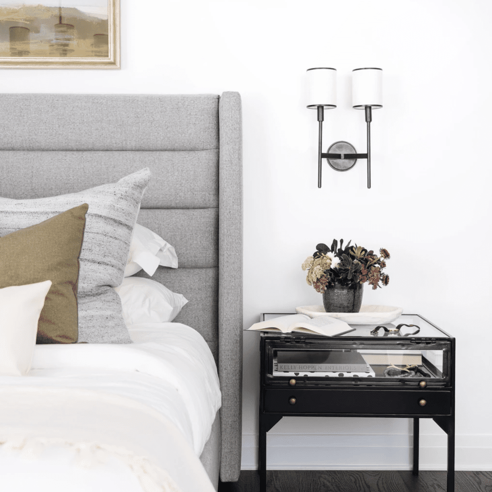 A bedroom with a contemporary-classic sconce