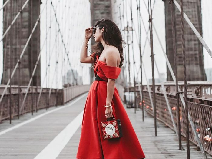 A young woman in a red dress holds a red purse and stands in the middle of a bridge in NYC