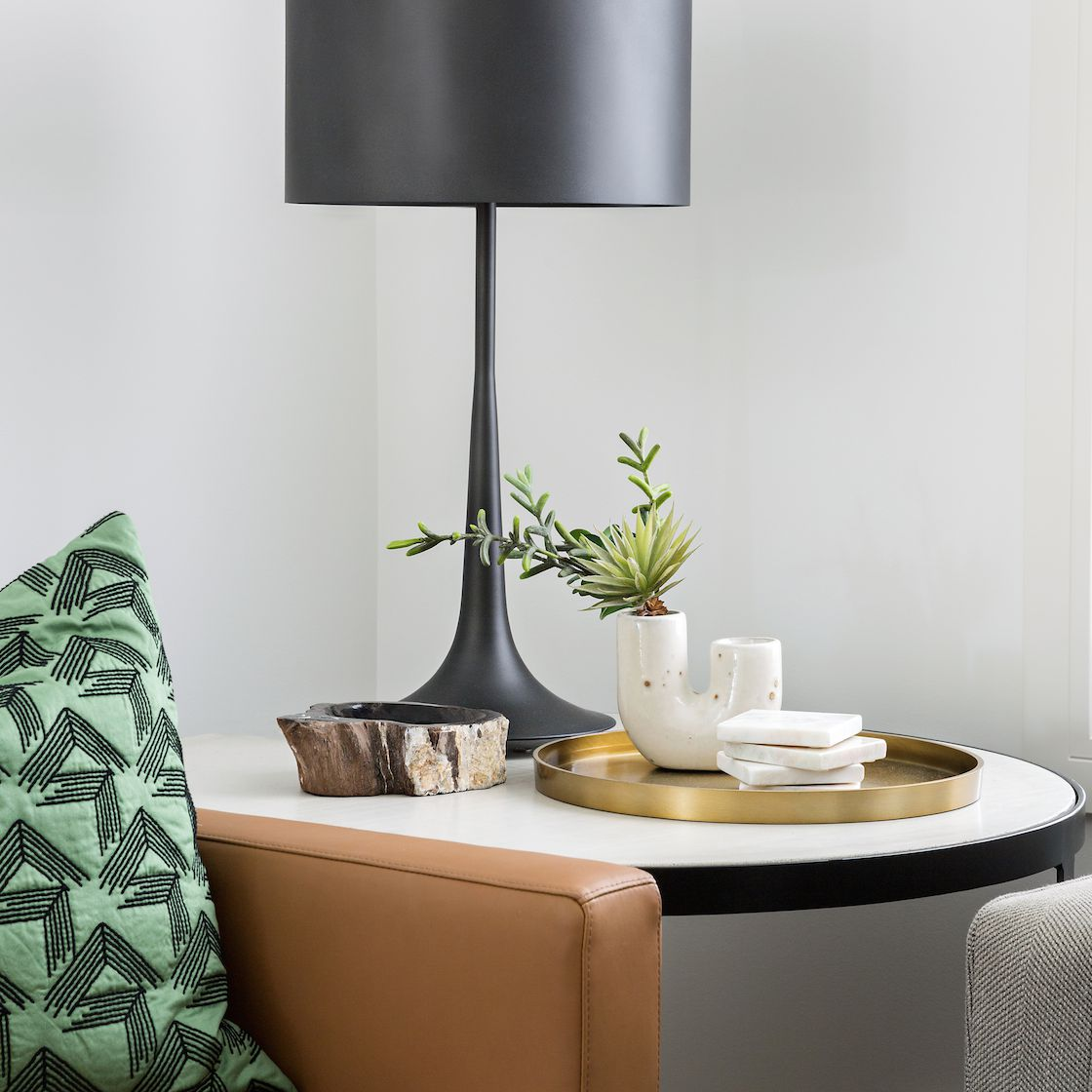 A side table topped with a sleek black lamp, a gold serving tray, and geometric white decor
