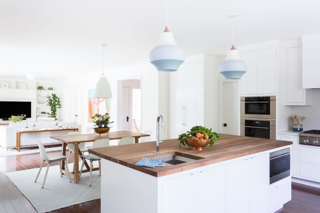 Open concept kitchen with blue pendant lights.