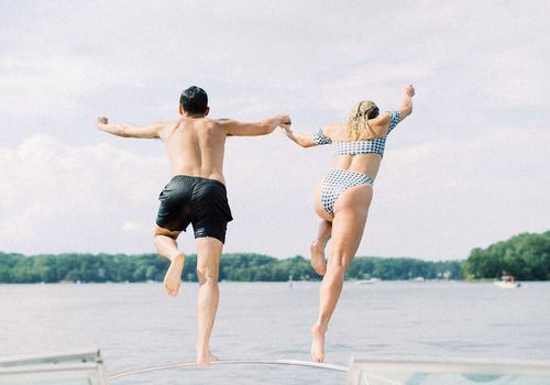 bride and groom jumping off boat