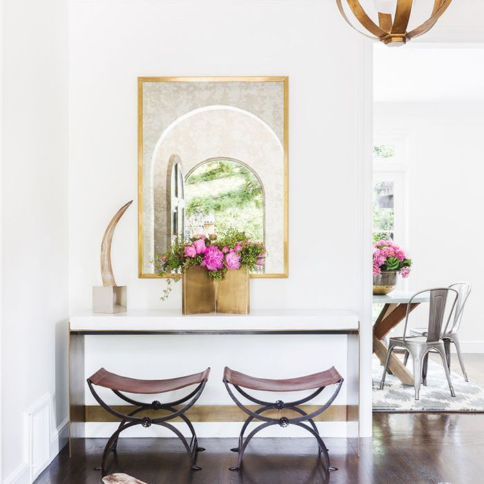 A textured rug and vanity featured in entryway with dining room in background