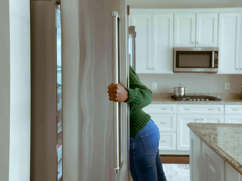 Woman looks into refrigerator
