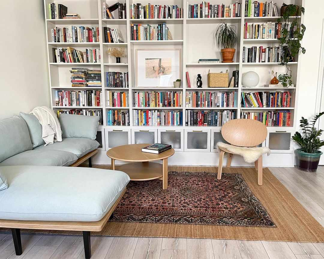 Large bookshelf wall filled with books and small cozy couch.