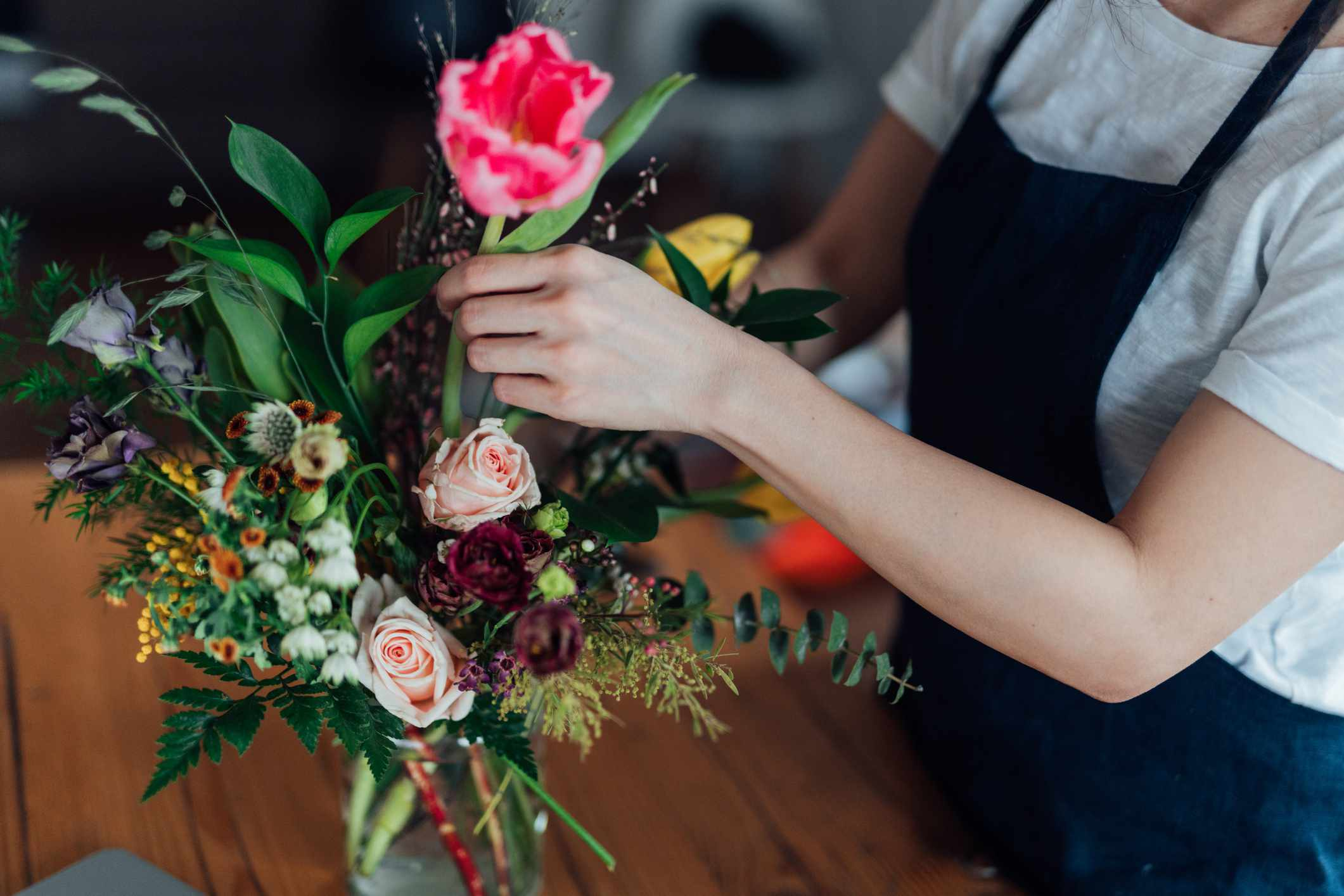 Cropped image of woman arranging flowers in vase