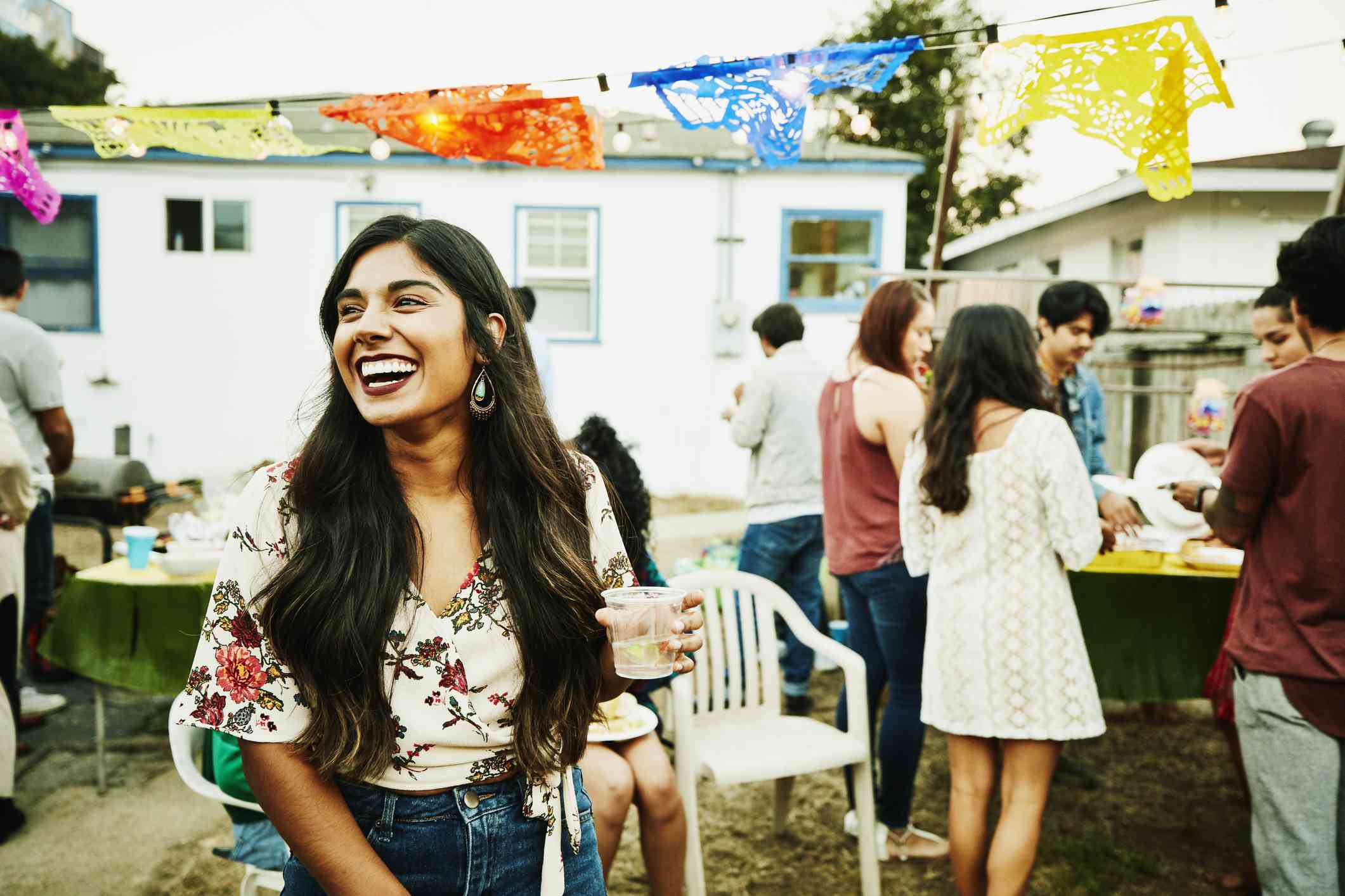 Smiling woman holds drink at backyard party