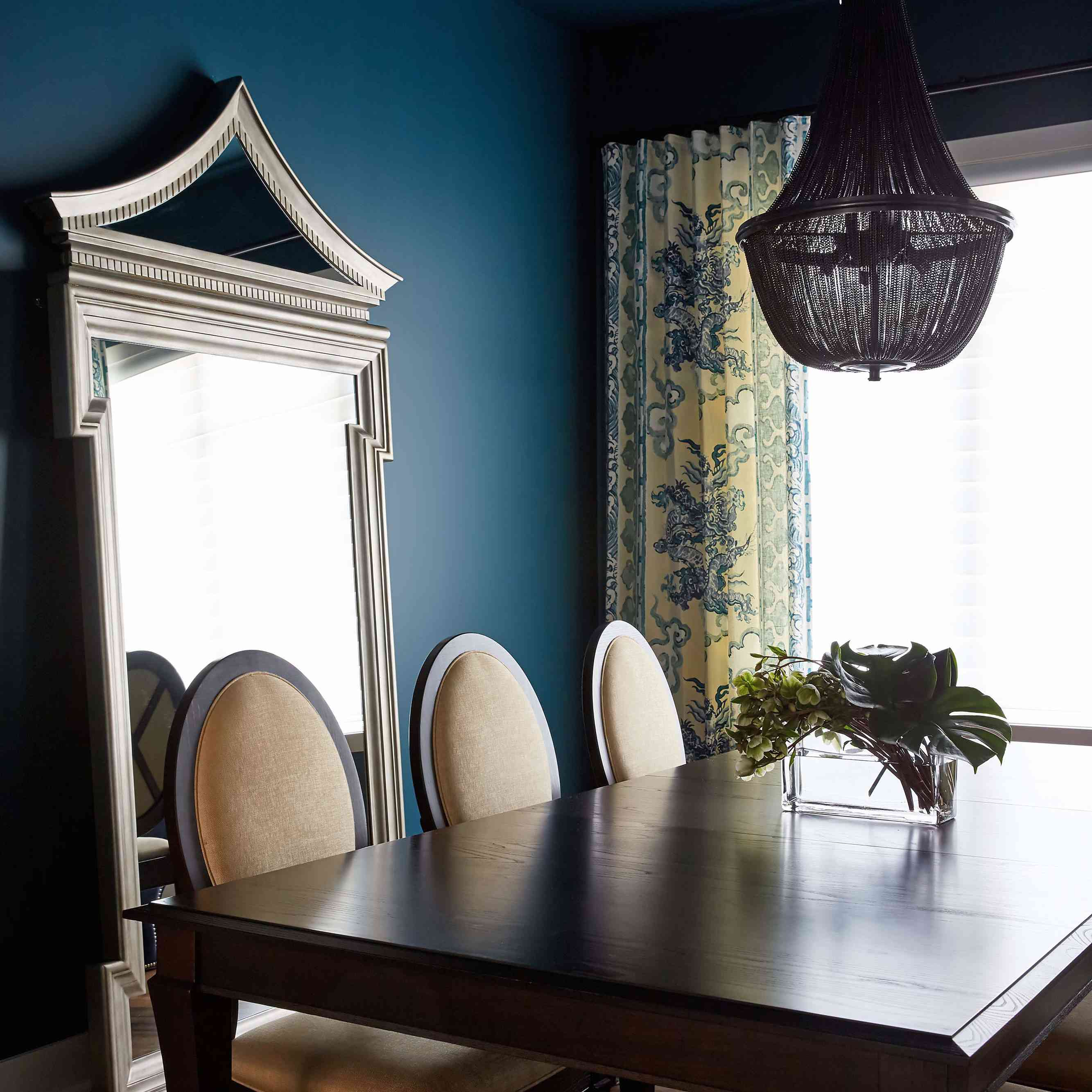 A dining room with navy walls, a navy ceiling, and printed beige and navy curtains