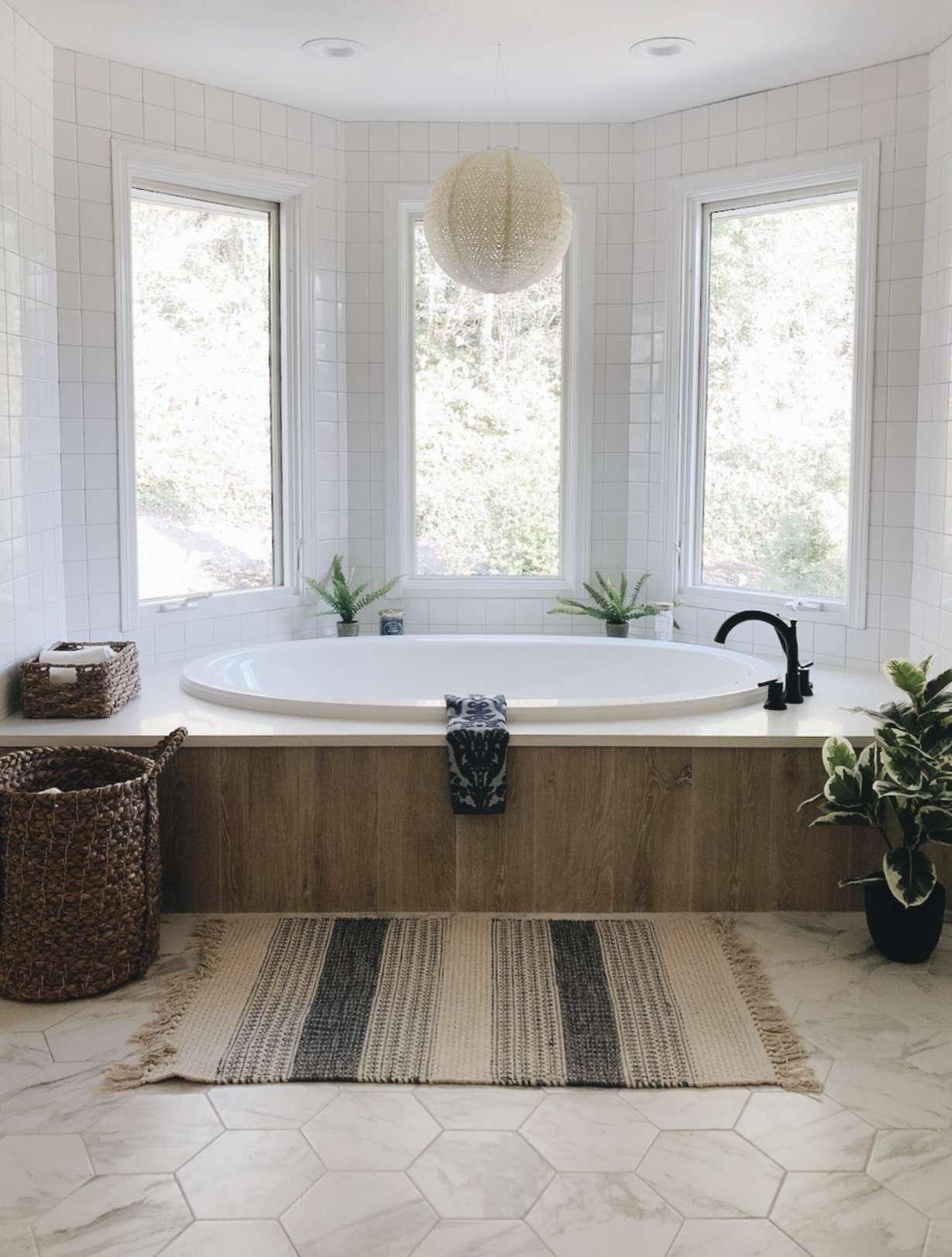 bathtub with bay windows, jute light fixture and rug