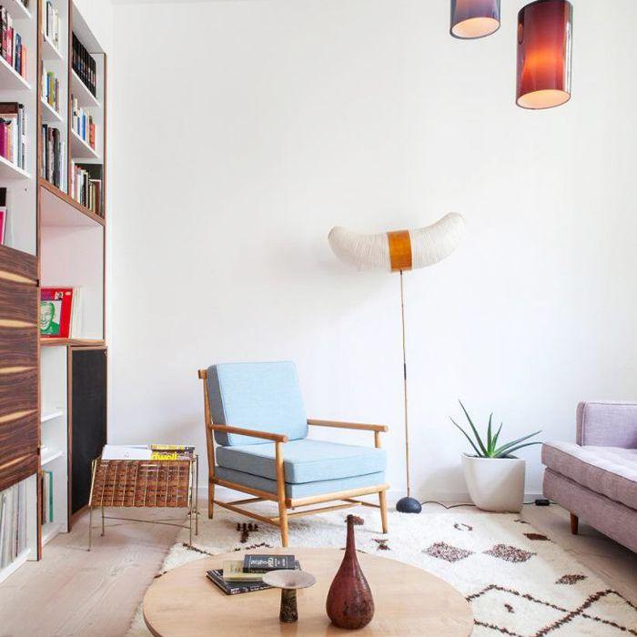 Una sala de estar con una pared de libros y un revistero junto a un sillón