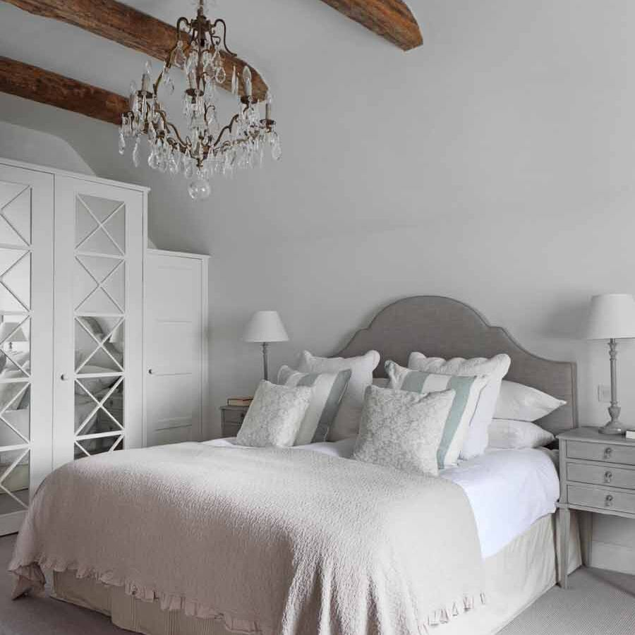 Formal primary bedroom with white armoire closet system.