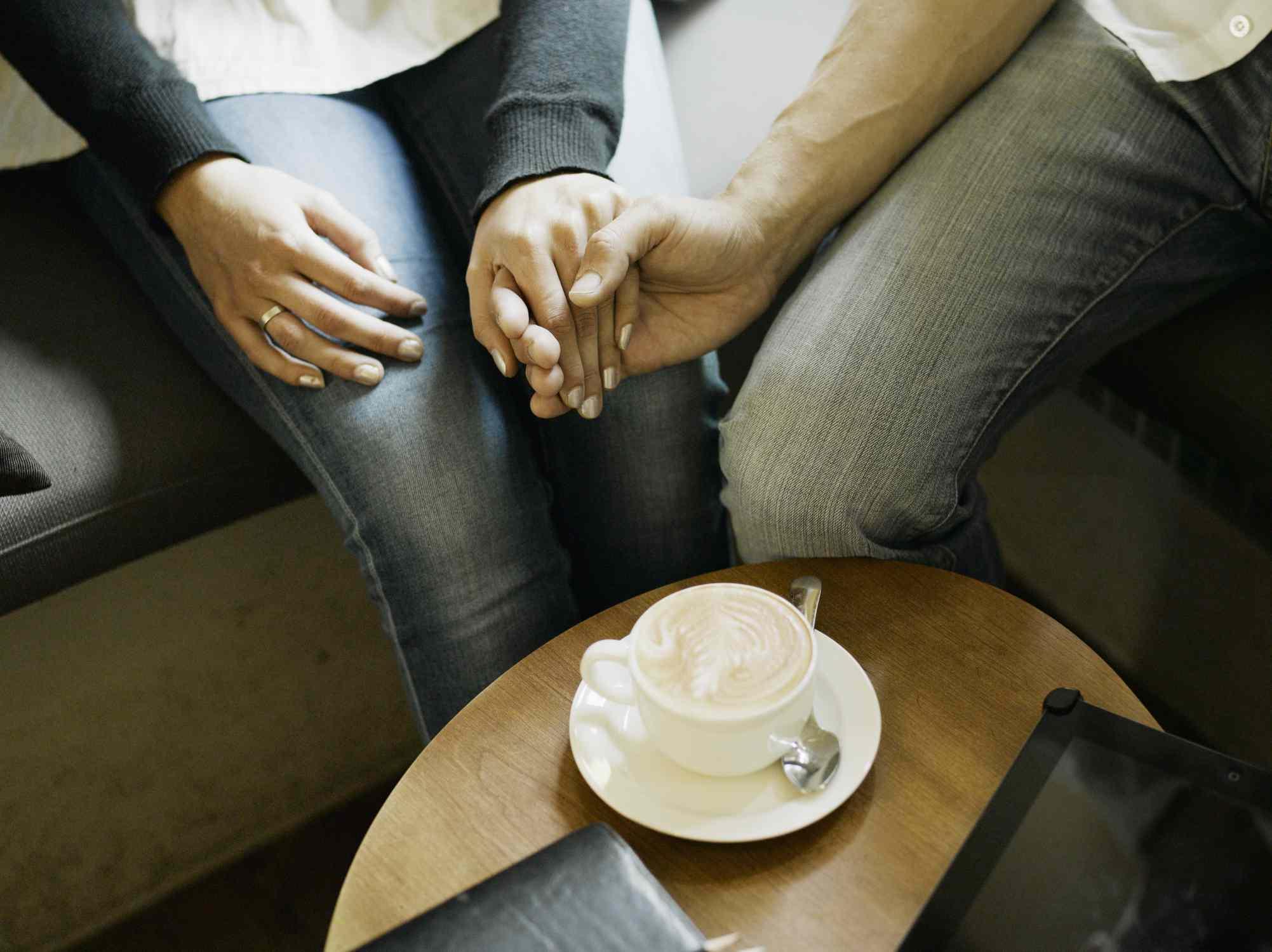 A couple on a coffee date holding hands.