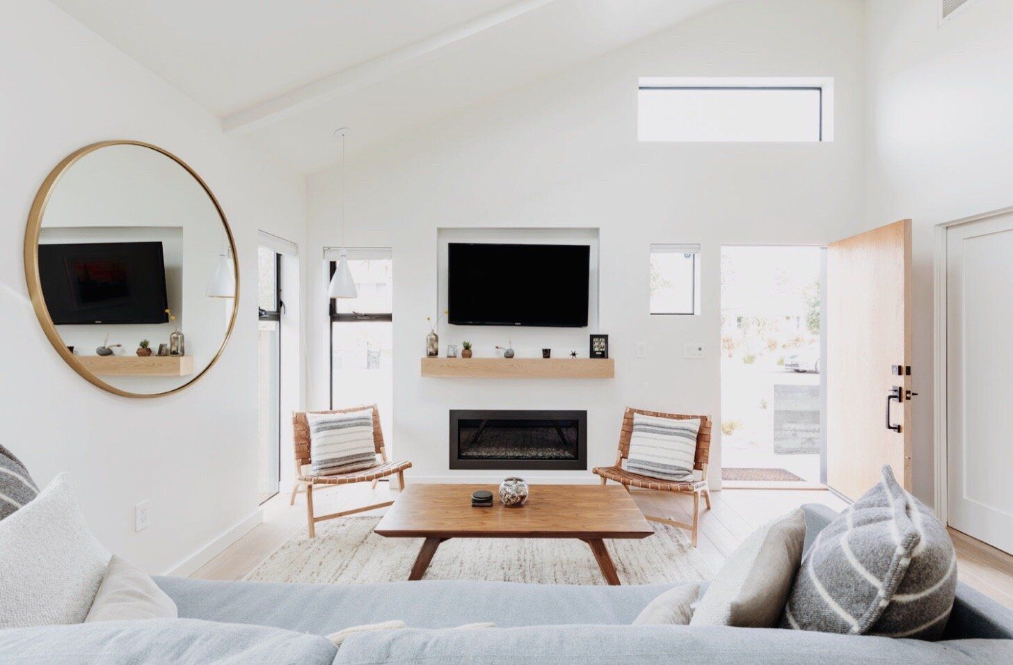 Bright white living room with wooden furniture.