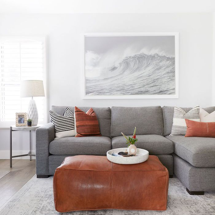 gray and brown modern living room, leather ottoman used as a coffee table