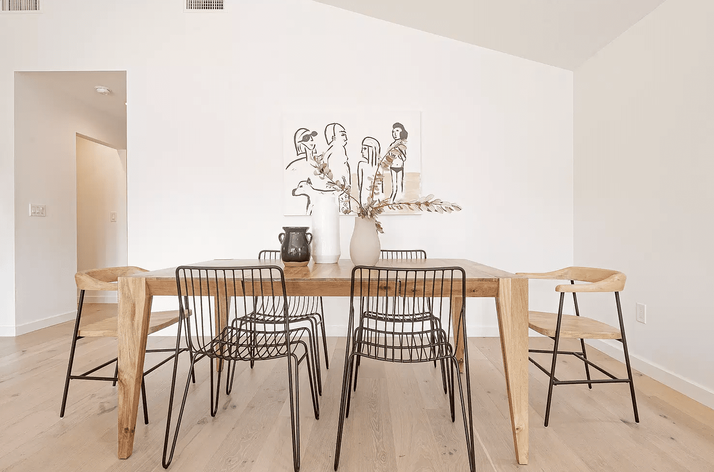 A dining room table surrounded by mixed-and-matched chairs