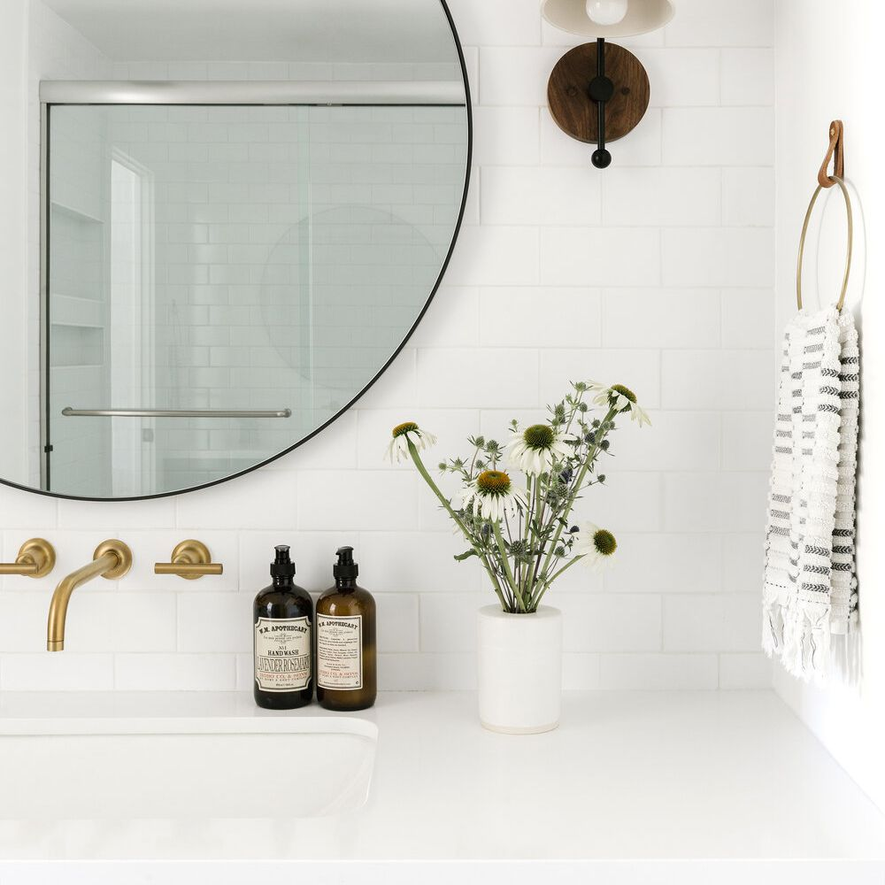 A bathroom lined with classic white subway tiles