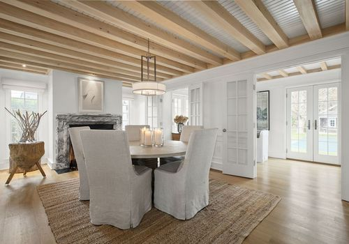 Neutral dining room with woven rug.