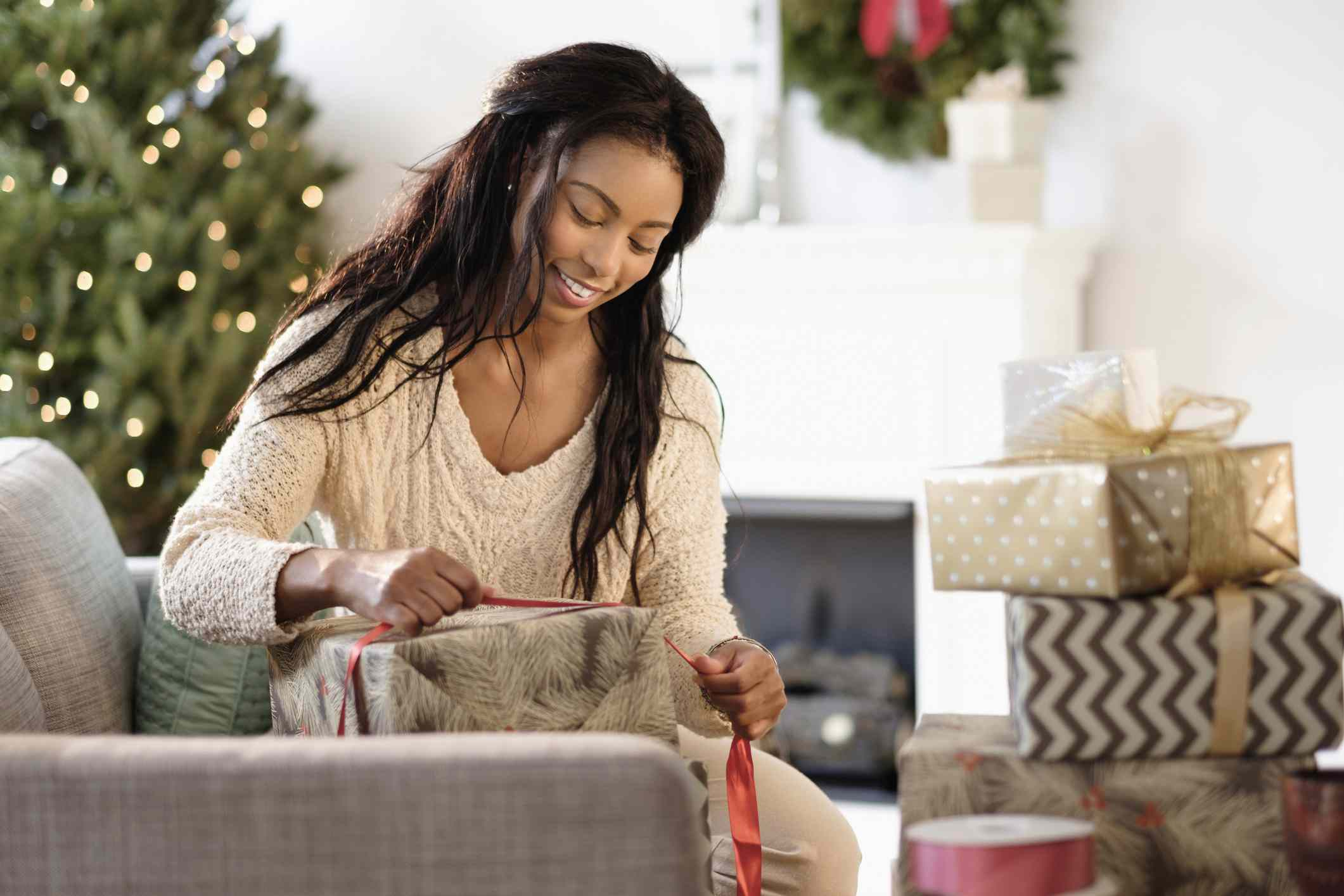 best gift exchange ideas - woman wrapping present on her couch