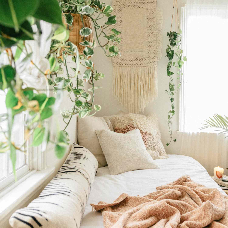 Pothos in hanging baskets in a boho bedroom.