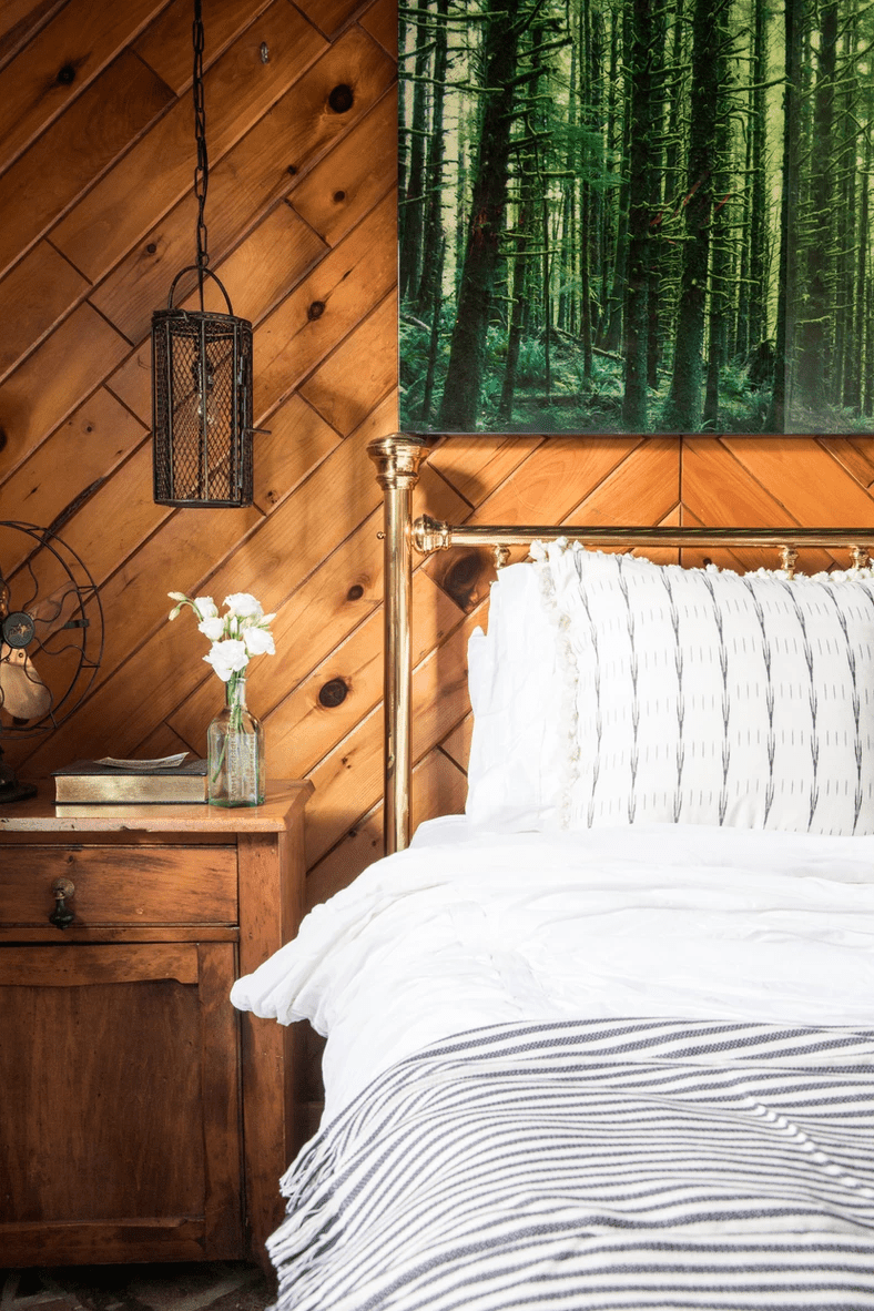 A wood-paneled bedroom with white linens
