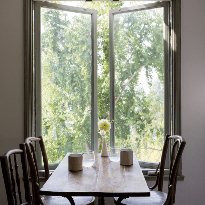 A small dining table with a single flower vase on it