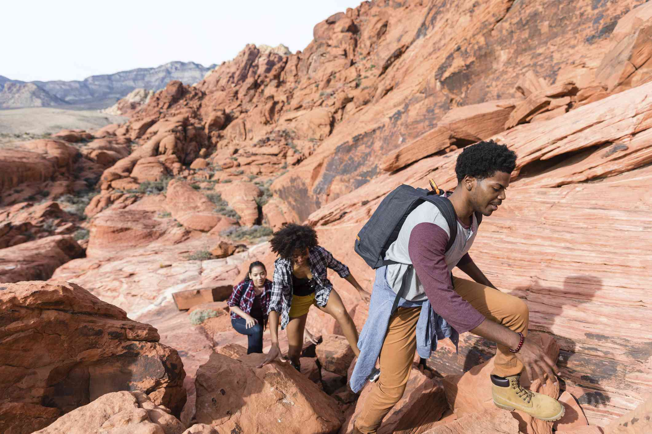 Friends hiking over rock formations