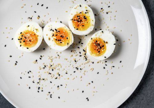 Halved hard boiled eggs with pepper on a white plate.