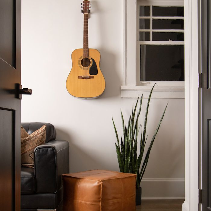 living room with wooden floor, aloe plant, guitar hanging on wall