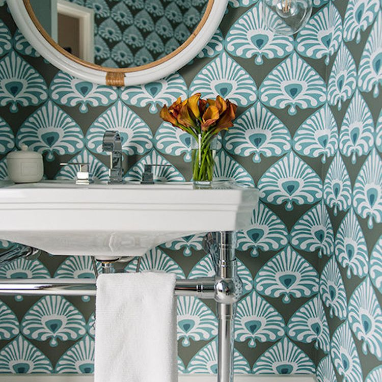 A bathroom lined with bold turquoise wallpaper