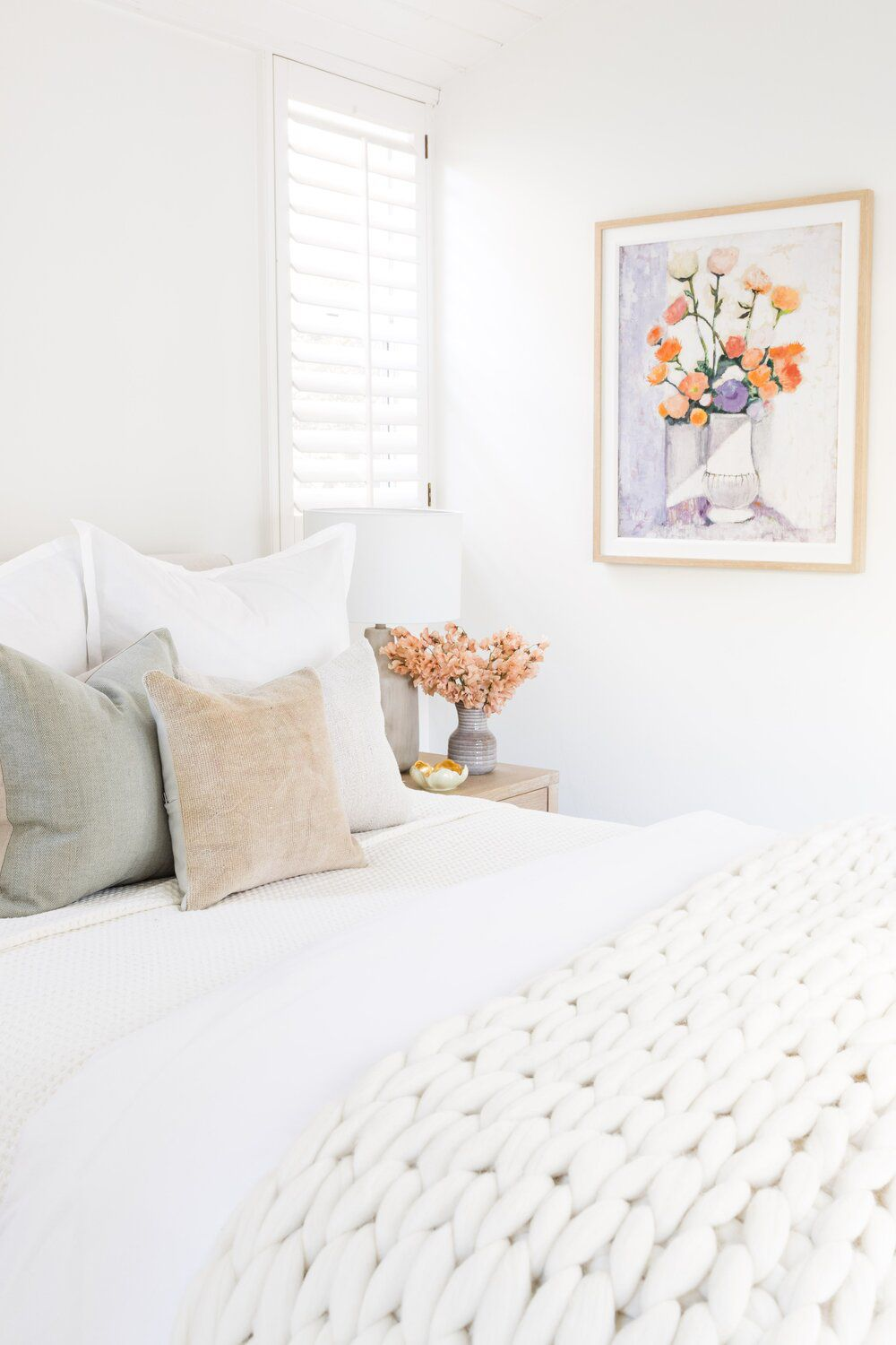A white bedroom with a lavender vase and a lavender painting of a bouquet