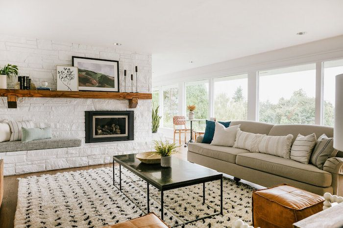 neutral modern living room white brick fireplace with bench seating leather footstool