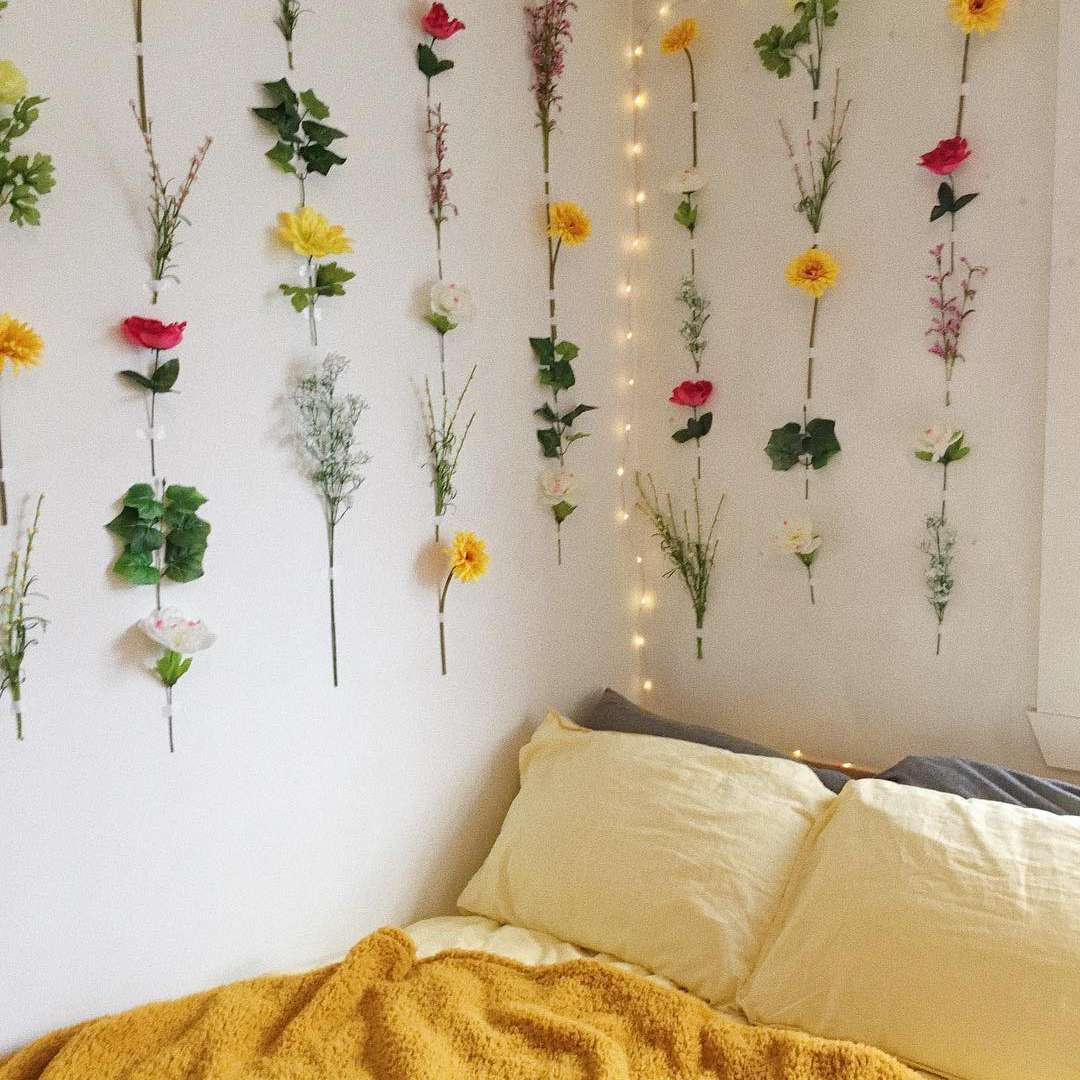 Dorm room with faux flowers pinned to wall.