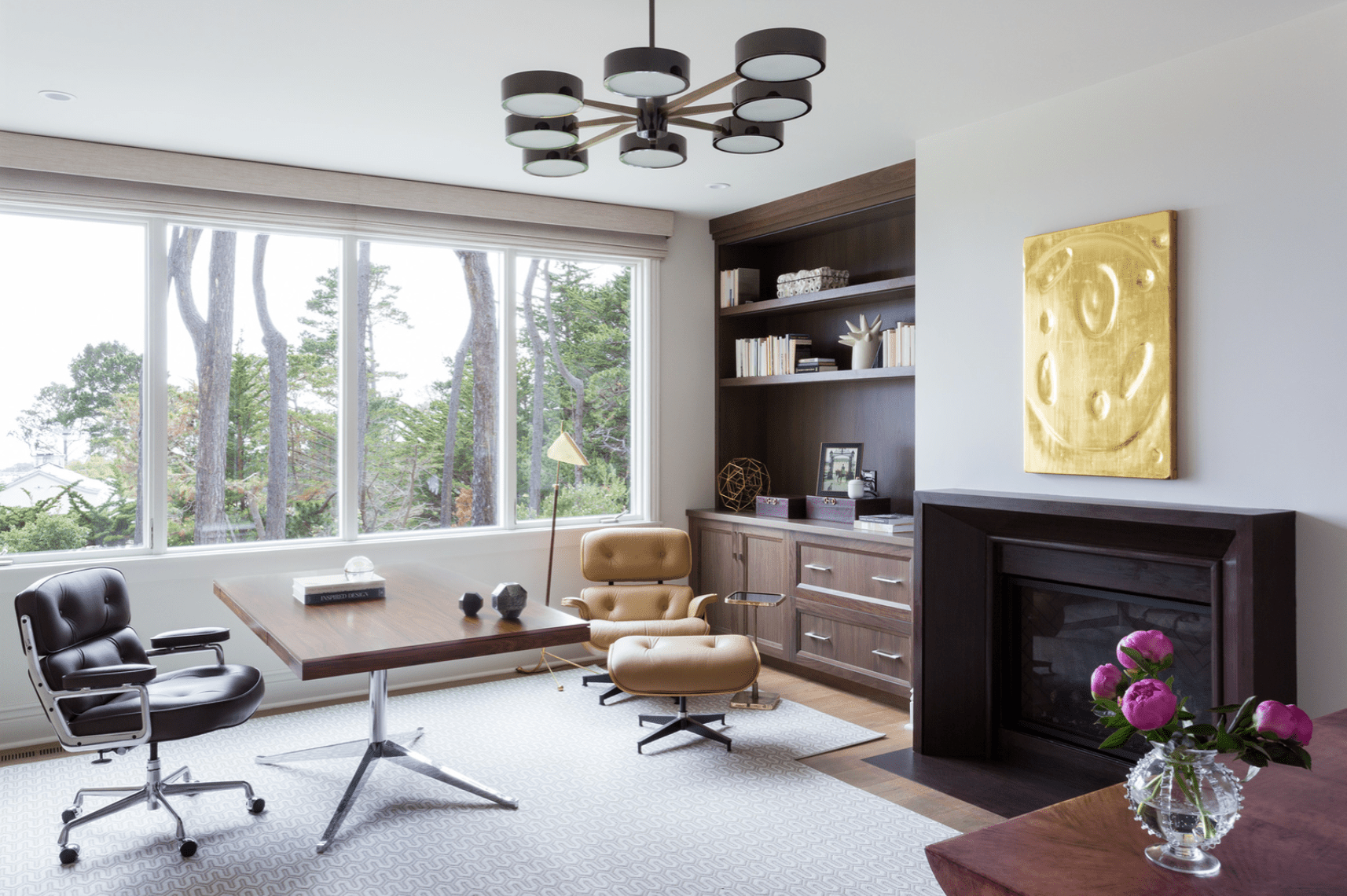 A wooden desk flanked by two chairs: a rolling desk chair and an upholstered lounge chair