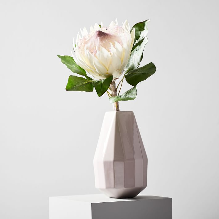 An artificial king protea flower in a white geometric vase.