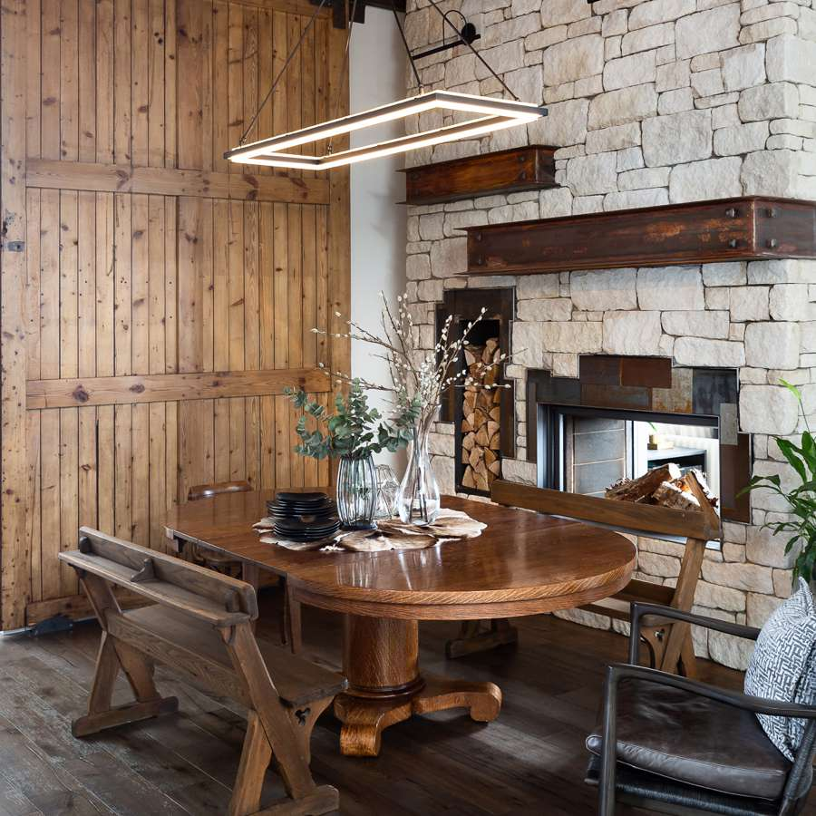 Rustic dining room with a stone wall, barn door, and bench seating