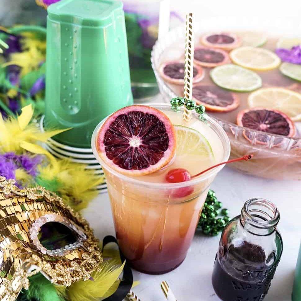 Cóctel en un vaso de plástico rodeado de una decoración con temática de Mardi Gras.