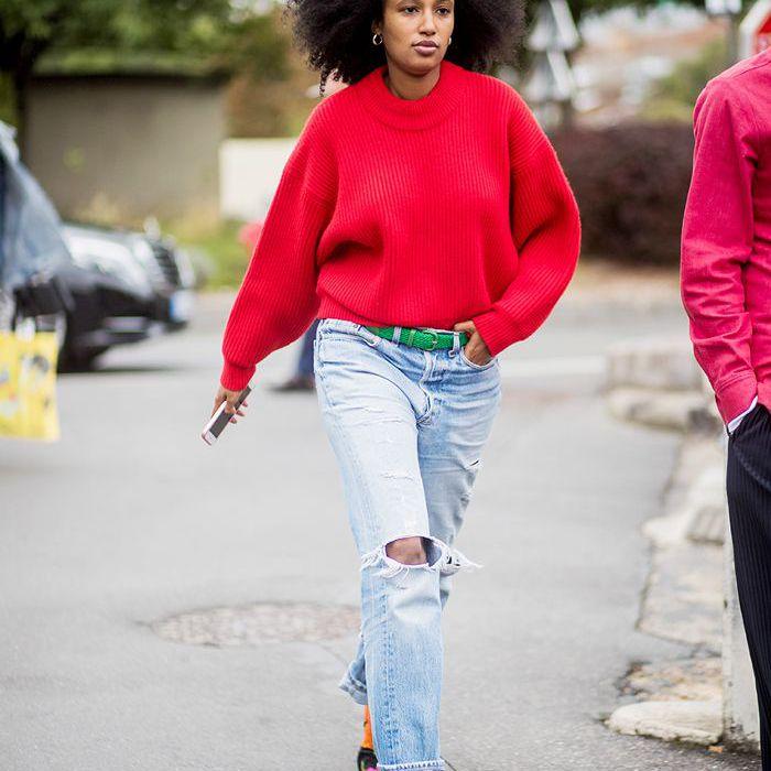 una mujer vestida con un suéter rojo brillante, jeans relajados y botas de media
