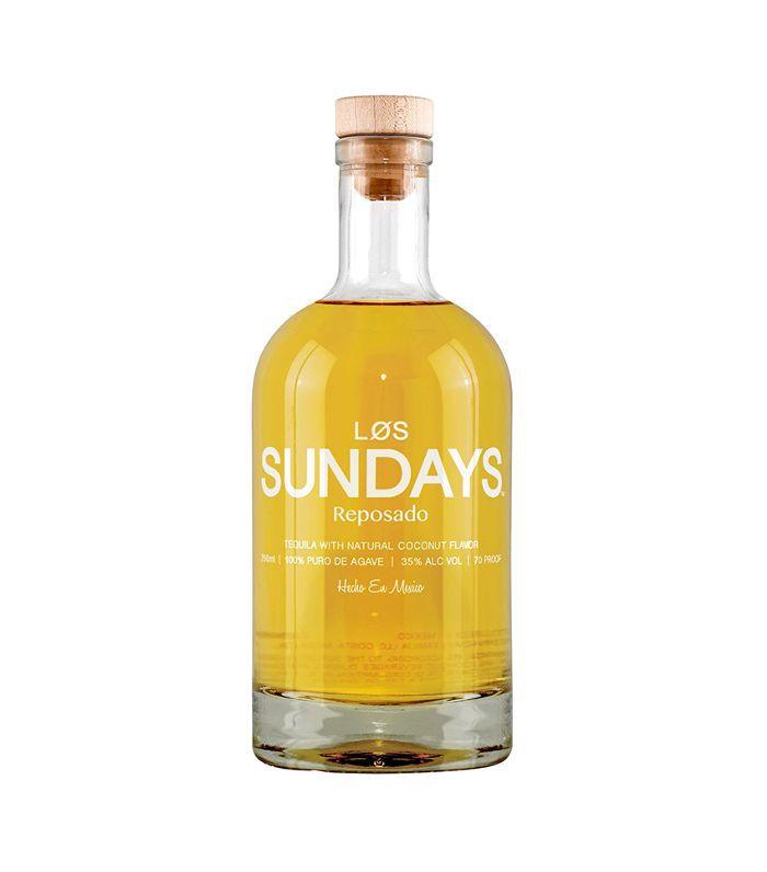 Una botella transparente llena de tequila amarillento.