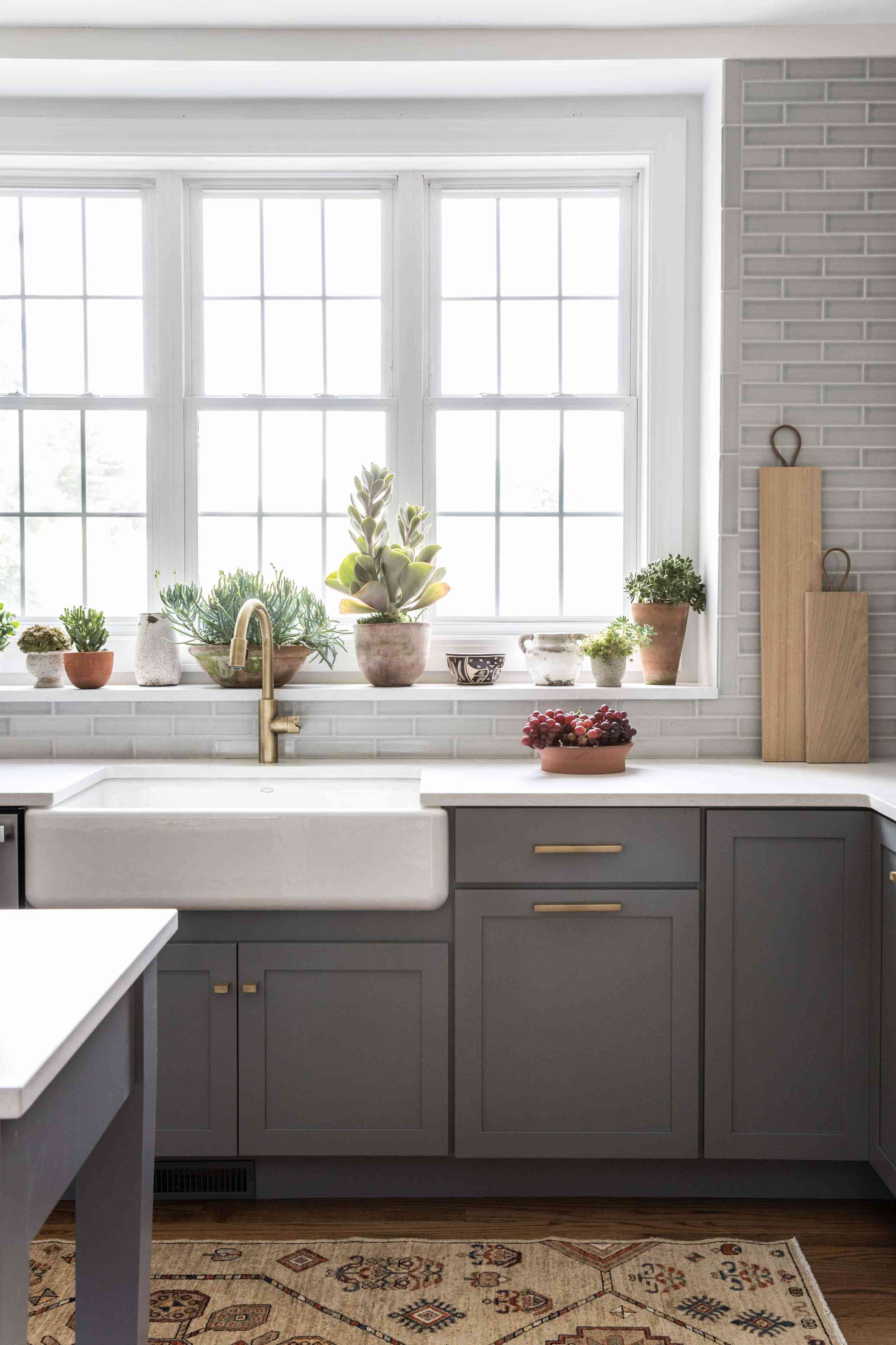 A kitchen with gray kitchen cabinets and a light gray tiled backsplash