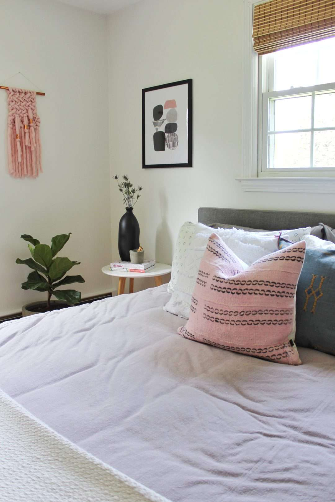 A bedroom with a lavender bedspread and pink and blue throw pillows
