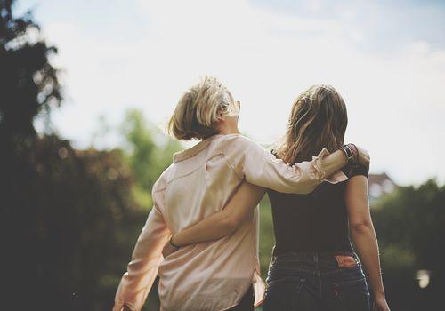 Vista posterior de mujeres caminando brazo alrededor al aire libre