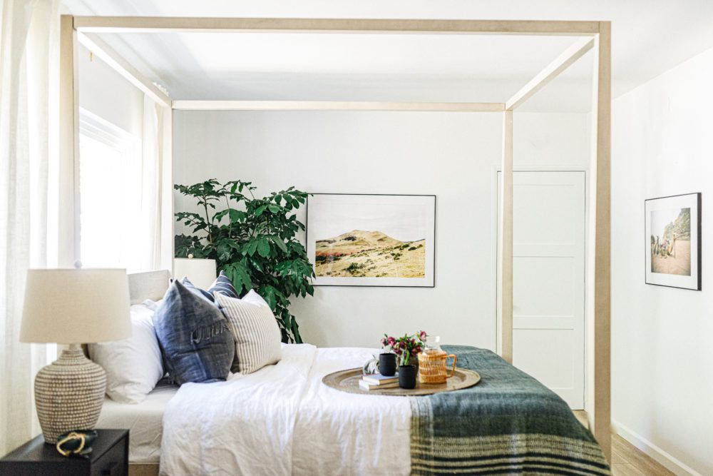 A canopy bed with blue linens on it
