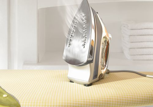how to clean an iron - clean iron soleplate on ironing board