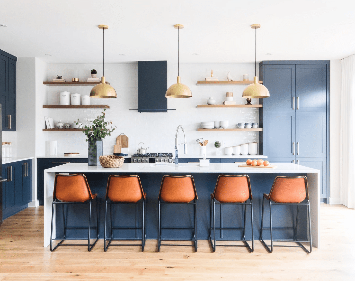 A kitchen with blue cabinets and orange barstools