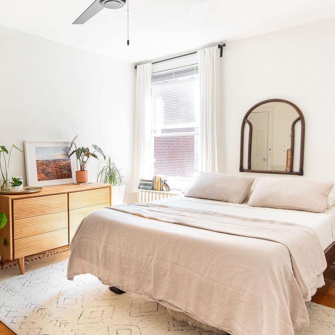 Light and airy bedroom with plush rug.