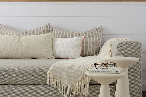 Soft neutral couch and small tables with glasses on top.
