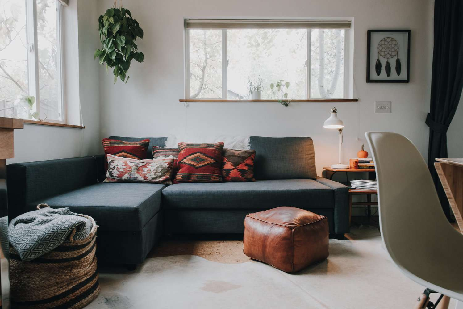 Living room that has a sofa with chaise lounge and ottoman pouf